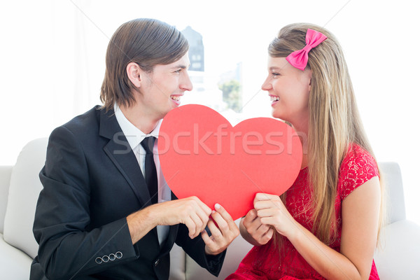 Cute geeky couple smiling and holding heart  Stock photo © wavebreak_media