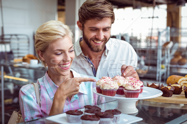 Cute couple on a date pointing chocolate cakes  Stock photo © wavebreak_media