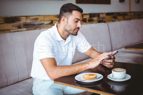 Young man having cup of coffee and pastry Stock photo © wavebreak_media