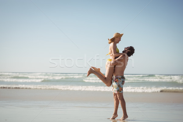 Stock photo: Side view of man lifting woman at beach