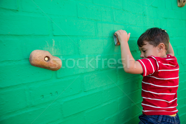 Stock photo: Rear view of boy climbing wall at playground
