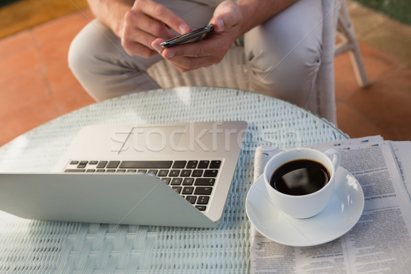 Mid section of man using mobile phone by laptop and coffee on table at cafe Stock photo © wavebreak_media