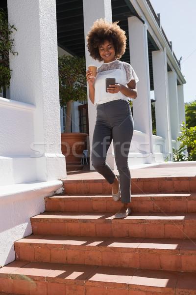 Femme souriante téléphone portable marche étapes téléphone Photo stock © wavebreak_media