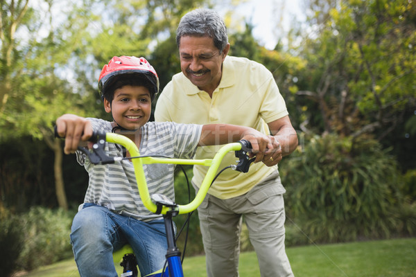 Grandfather assisting grandson while riding bicycle Stock photo © wavebreak_media