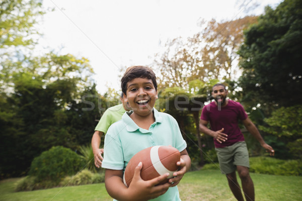 Boy playing rugby with father and grandfather at park Stock photo © wavebreak_media