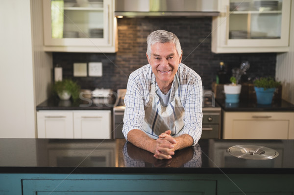 Smiling senior man leaning on kitchen counter at home Stock photo © wavebreak_media