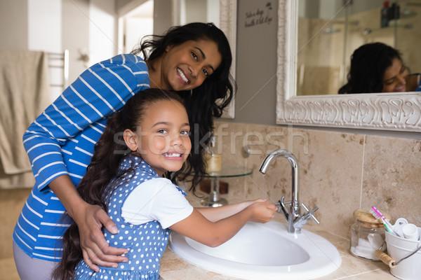 Smiling girl with mother washing hands at bathroom sink Stock photo © wavebreak_media