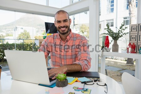 Smiling graphic designer using tablet at desk in office Stock photo © wavebreak_media