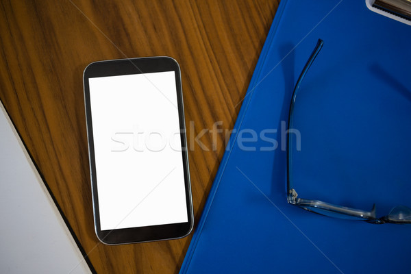 High angle view of phone and clipboard on table in office Stock photo © wavebreak_media