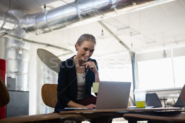 Young businesswoman using laptop in office Stock photo © wavebreak_media