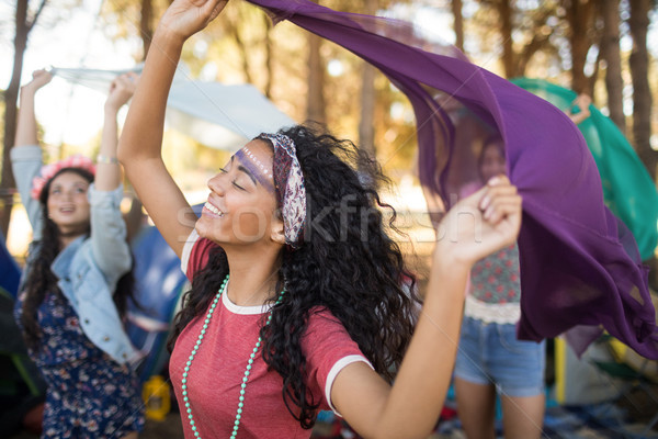 Stock photo: Woman with female friends holding scarfs at campsite