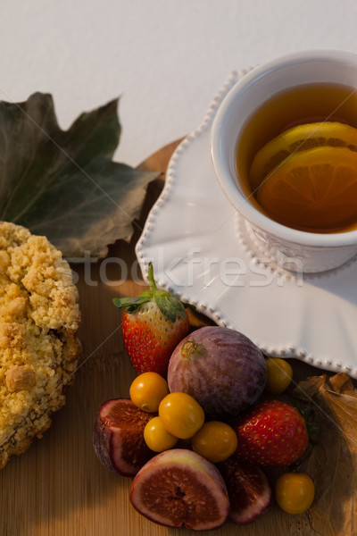 Various fruits, autumn leaves and cup of green tea on chopping board Stock photo © wavebreak_media