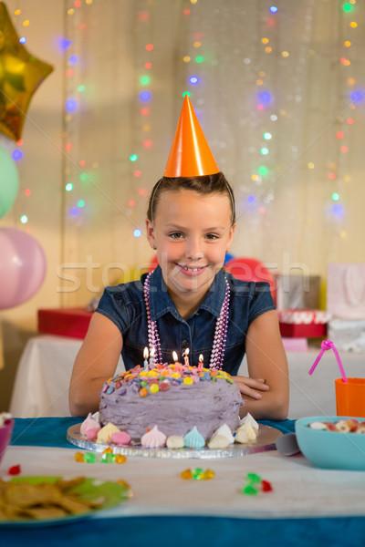 Girl standing with birthday cake at home Stock photo © wavebreak_media