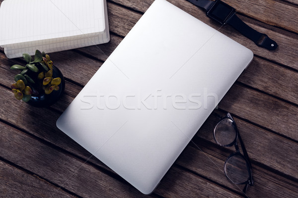 Overhead of laptop, diary, pot plant, spectacles and smart watch on wooden table Stock photo © wavebreak_media