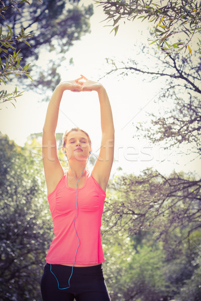 Blonde athlete stretching arms with eyes closed Stock photo © wavebreak_media