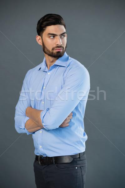 Handsome man posing against grey background Stock photo © wavebreak_media