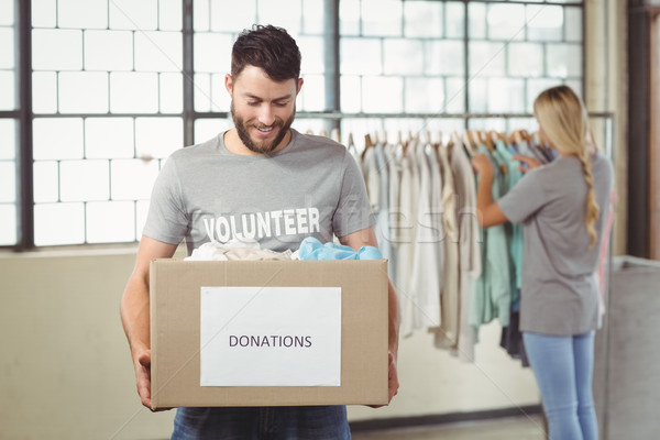 Man holding clothes donation box with woman in background Stock photo © wavebreak_media