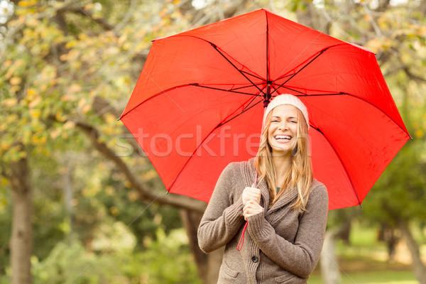 Smiling young woman under umbrella Stock photo © wavebreak_media