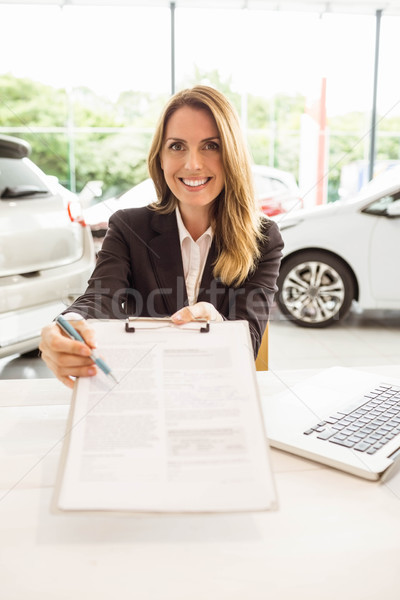 Smiling saleswoman holding a clipboard Stock photo © wavebreak_media