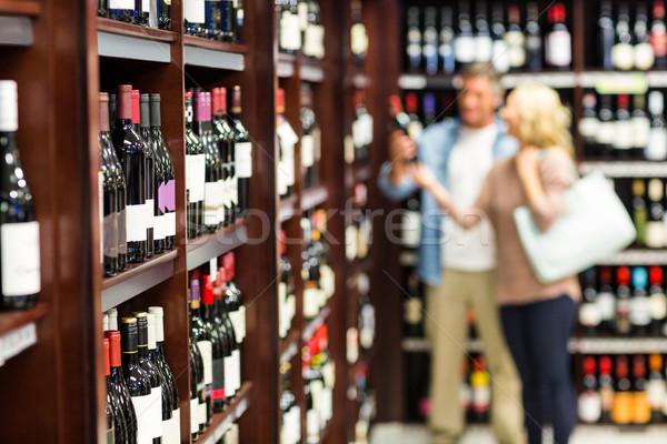 Uśmiechnięty para patrząc butelki wina supermarket Zdjęcia stock © wavebreak_media