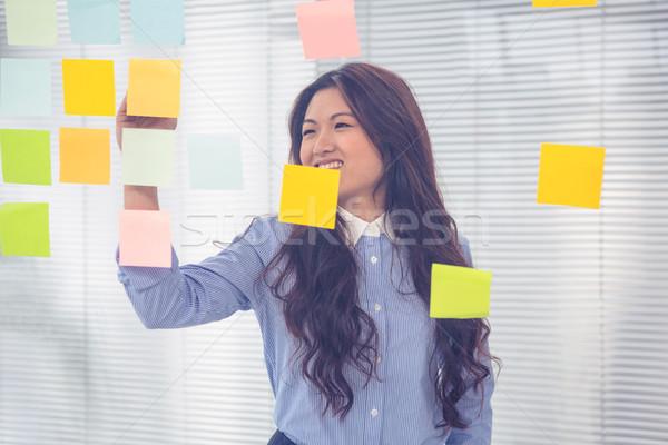 Asian businesswoman using sticky notes on wall Stock photo © wavebreak_media