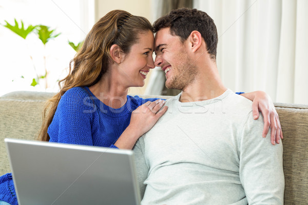 Young couple smiling face to face on sofa and using laptop Stock photo © wavebreak_media