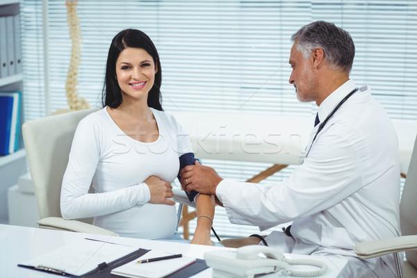Doctor measuring pressure of pregnant woman Stock photo © wavebreak_media