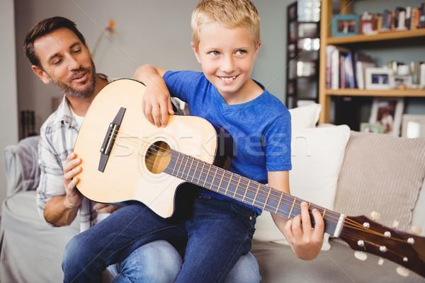 Happy man teaching guitar to son at home Stock photo © wavebreak_media