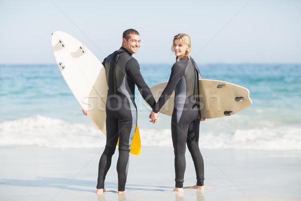 Pár szörfdeszka tart kéz tengerpart napos idő Stock fotó © wavebreak_media
