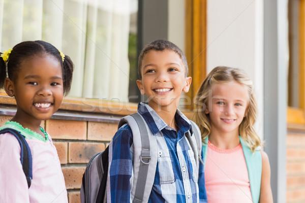 Uśmiechnięty szkoły dzieci stałego korytarz dziewczyna Zdjęcia stock © wavebreak_media