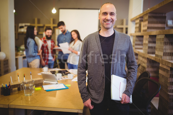 Confident businessman standing by table in creative office Stock photo © wavebreak_media