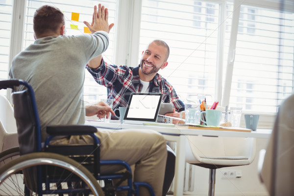 Handicap businessman giving high-five to colleague in office Stock photo © wavebreak_media