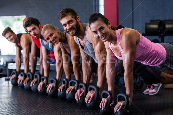 Portrait of smiling friends doing push-ups with kettlebell in gym Stock photo © wavebreak_media