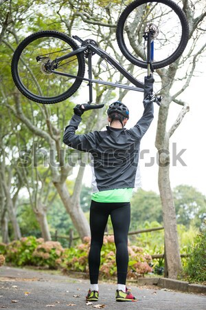 Stock photo: Male cyclist carrying mountain bike