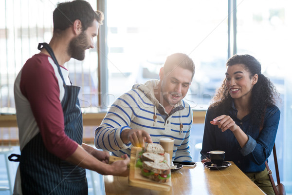 Waiter serving a plate of sandwich to customer Stock photo © wavebreak_media