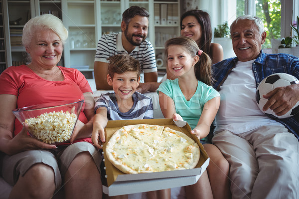 Multi-generation family sitting with popcorn and pizza while watching soccer match Stock photo © wavebreak_media