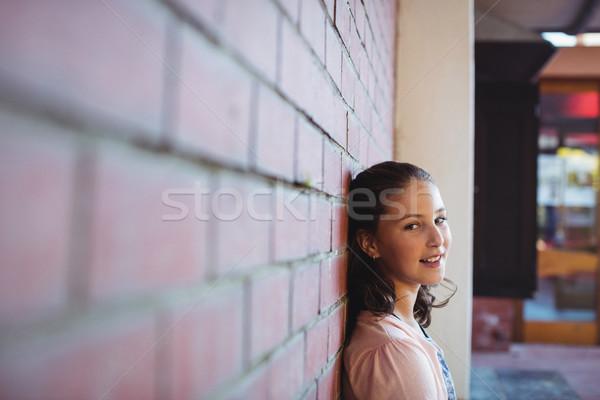 Boldog iskolás lány ül téglafal iskola kampusz Stock fotó © wavebreak_media