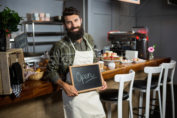 Portrait of smiling male staff holding chalkboard with open sign at counter Stock photo © wavebreak_media