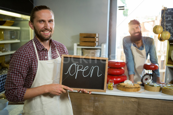 Smiling male staffs holding a open sign Stock photo © wavebreak_media