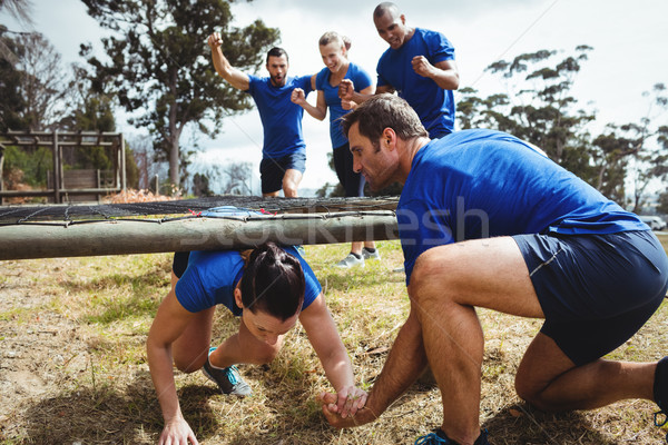 Fit woman crawling under the net during obstacle course while fit people cheering Stock photo © wavebreak_media