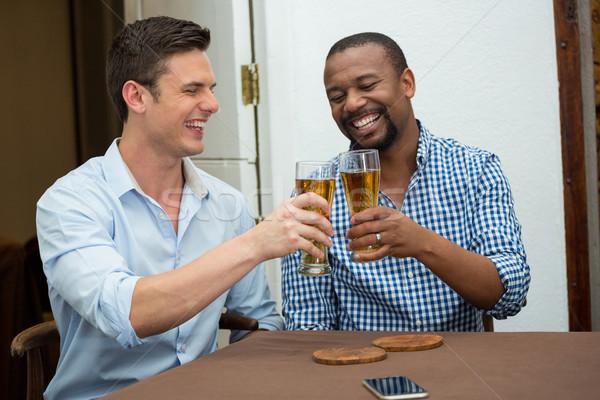 Men toasting beer glasses at restaurant table Stock photo © wavebreak_media