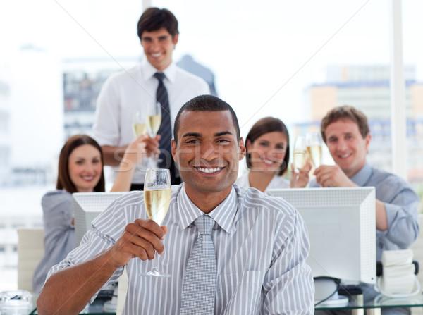 Fortunato squadra di affari bere champagne ufficio sorriso Foto d'archivio © wavebreak_media