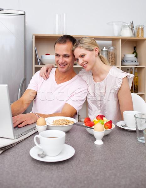 Enamored couple using a laptop while having breakfast  Stock photo © wavebreak_media