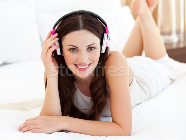 Charming woman lying down on bed listening music Stock photo © wavebreak_media