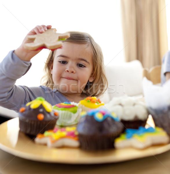 Happy little girl eating confectionery at home Stock fotó © wavebreak_media