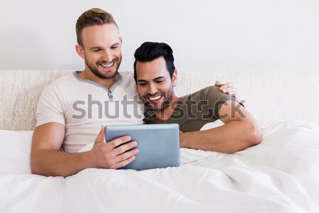 Laughing couple using a laptop in the bedroom Stock photo © wavebreak_media