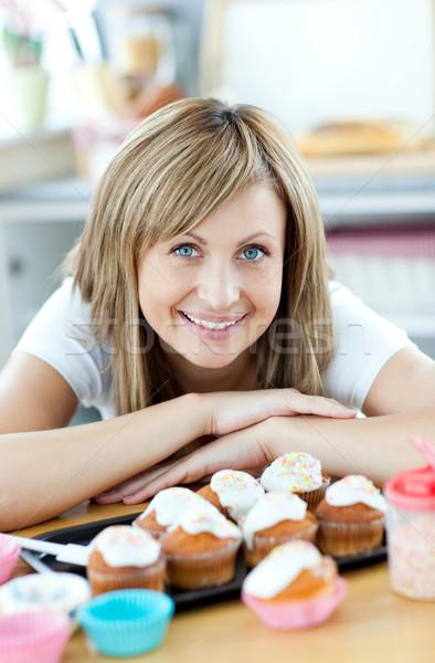Encantado mulher alimentação bolos cozinha casa Foto stock © wavebreak_media