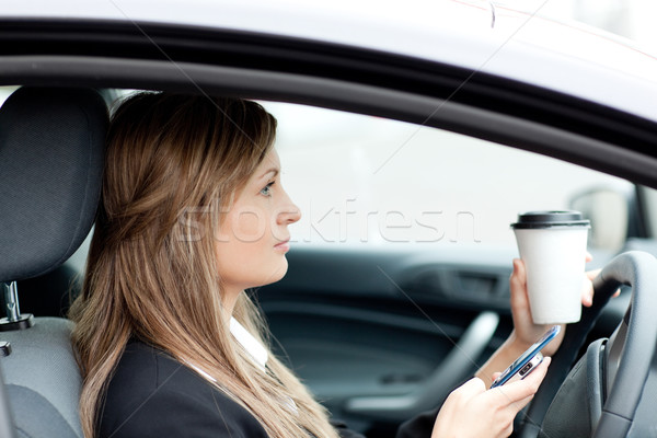 Blond businesswoman sending a text while driving Stock photo © wavebreak_media