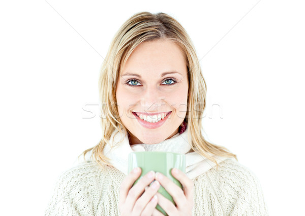 Smiling blond woman wearing a pullover and holding a cup of coffee against a white background Stock photo © wavebreak_media