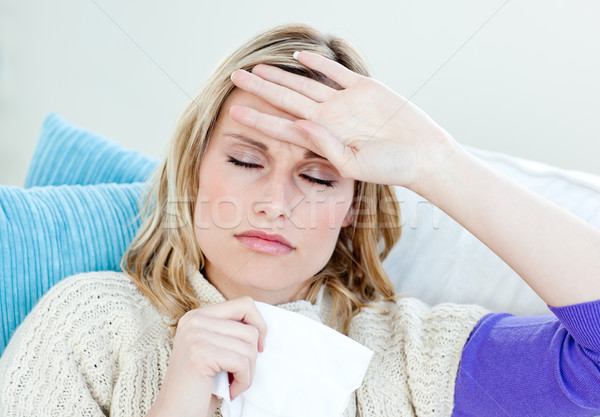 Sick woman with headache lying on the sofa in the living-room at home Stock photo © wavebreak_media